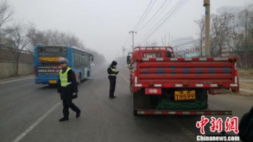 资料图:2015年12月8日下午,京开高速路辅路大庄桥路段,环境监察人员检查路上行驶的大货车。张尼 摄