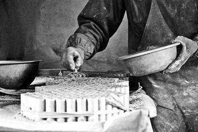 在浏阳一个花炮车间,技师小心地将药珠装进筒管。