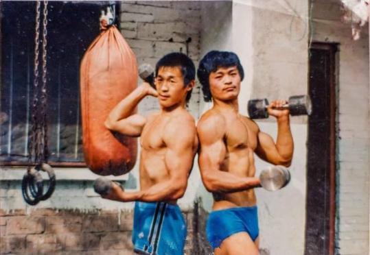 图为爷爷和村庄的叔叔拿着哑铃锻炼肱二头肌。