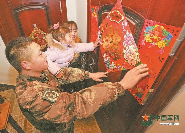 """第1集团军某防空旅四级军士长雍自勇一家三口在公寓房门前贴""""福""""迎春。"""