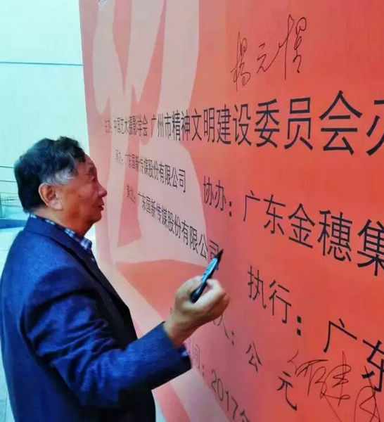 中国艺术摄影学会主席杨元惺在主展板上签名(罗景尧摄)