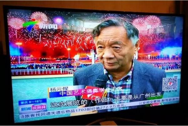 中国艺术摄影学会主席杨元惺在展品前接受广东电视台采访
