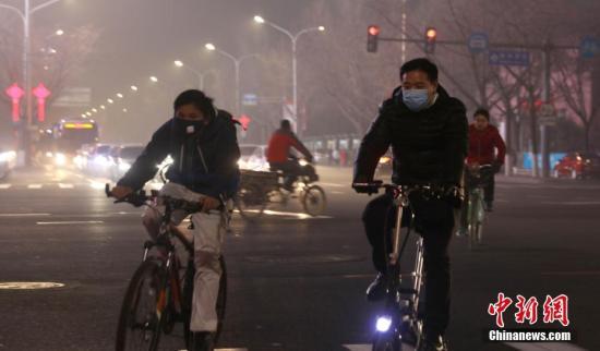 资料图:北京持续重度雾霾天气,民众戴口罩骑行在街头。中新社记者 杨可佳 摄