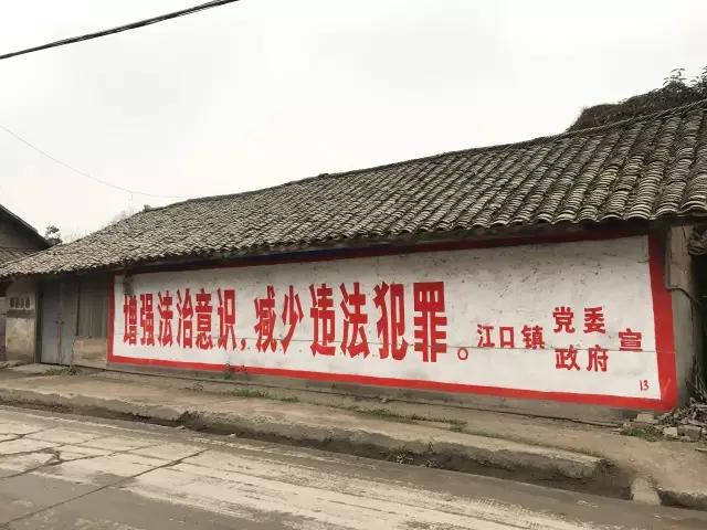 """江口镇一处民房粉刷着一行标语,""""增强法治意识,减少违法犯罪。"""""""