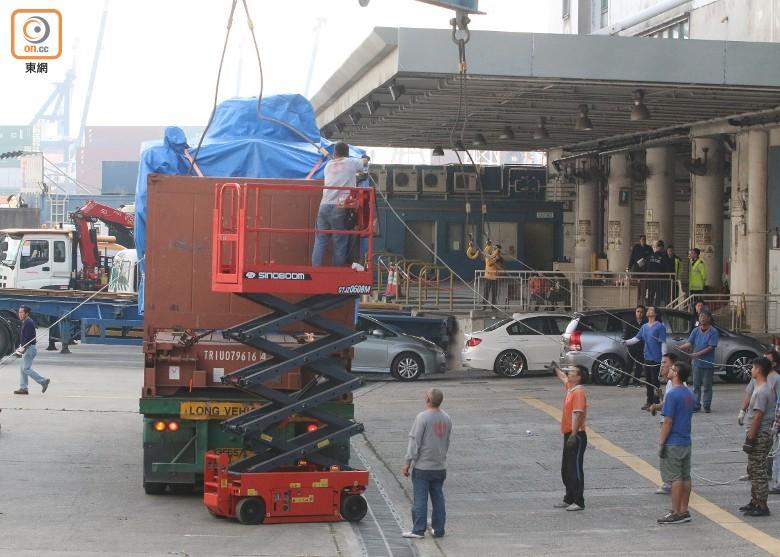 工作人员协助把装甲车吊上货车/来源:东网
