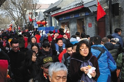 """29日,游客们在南锣鼓巷游玩。鸡年春节是南锣鼓巷改造后首次""""开门迎客""""。"""