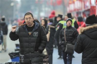 1月28日,龙潭庙会,旅客正在吃肉串。