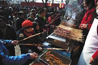 1月31日,欢然亭公园厂甸庙会,旅客们在小吃摊位前采办羊肉串。