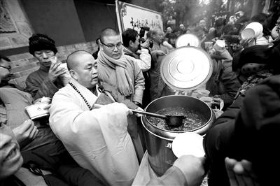 2017年1月5日,河南登封,农历腊月初八,祈福法会结束后,释永信为游客施粥供图/东方IC