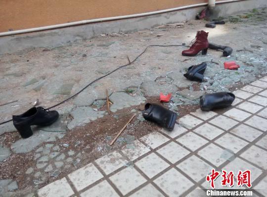 5幢楼的背面,地上散落了一地的玻璃渣、筷子、硬币和女士高跟鞋等。 王逸飞 摄