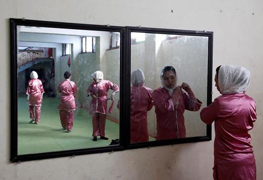 当地时间1月19日,19岁的Hatifa Rezai(右)在习武前对镜整理头巾