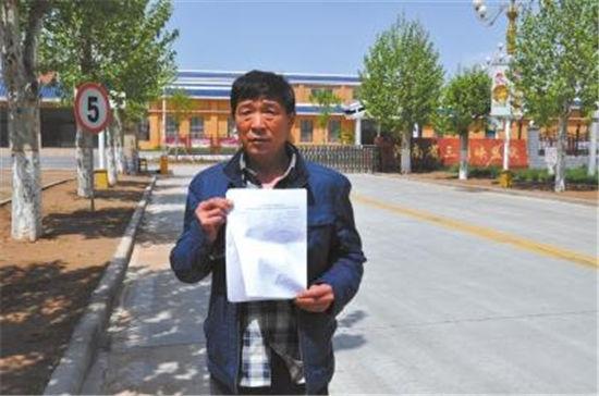 刘开国拿着检测陈述在河南省三门峡牢狱门口。