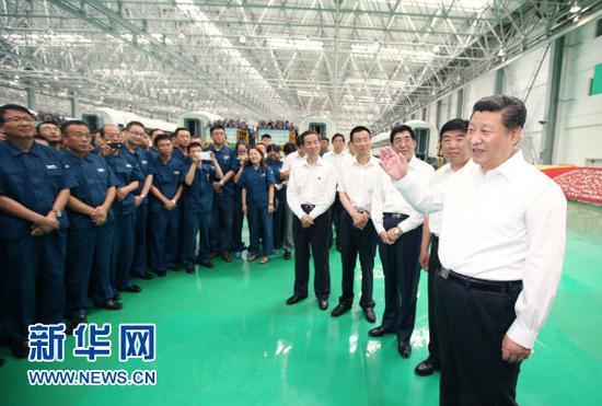 图为:2015年7月17日,习近平在中国中车长春轨道客车股份有限公司考察时同现场职工交流。
