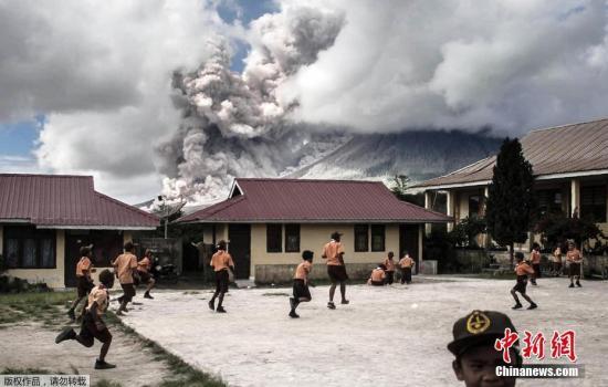 印尼锡纳朋火山喷发 学生不惧火山灰淡定玩耍(图)