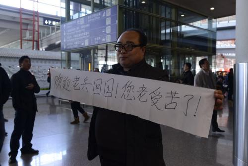 """一名姓李的老师,看到新闻得知国家老兵返国的音讯,自觉赶到机场接机,手持""""欢送老兵返国,您老辛劳了!""""的横幅。中新网记者 富宇 摄"""