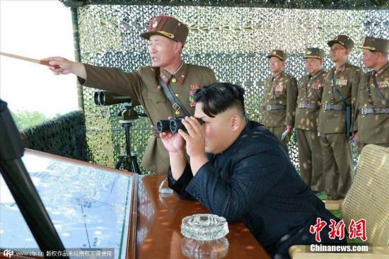 资料图:2015年6月18日消息,据朝鲜《劳动新闻》报道,金正恩近日视察朝鲜炮兵射击比赛,与士兵合影留念喜笑颜开。 CFP视觉中国
