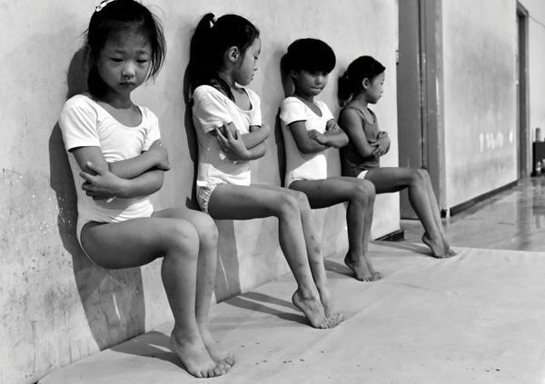 中国徐州,一所体操学校的四名学生在做下午30分钟的脚趾压力训练。