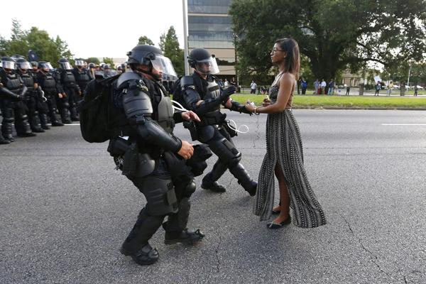 """在美国路易斯安那州的一场游行中,一位身着长裙手无寸铁的年轻黑人女性淡然面对全副武装的警察,这一幕被摄影师乔纳森・巴赫曼(Jonathan bachman)记录下来,在网络上发布后引起剧烈反响,美国《华盛顿邮报》称这名女士是""""虎穴中的优雅""""、""""暴风中心的宁静""""。"""