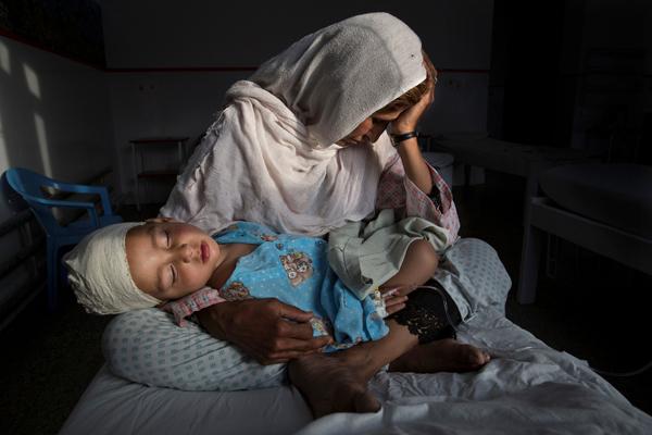 2016年3月29日,阿富汗,一名妇人抱着在一次炸弹袭击中受伤的侄儿。2016年上半年,至少有1600人死亡,超过3500人受伤。尽管政府花费了数十亿美元来稳定这个国家,但是在整体上却并没有什么改变。