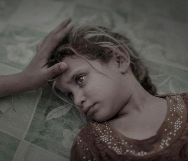 由于伊拉克和库尔德部队发起了一项军事行动,一名五岁的小女孩从苏摩尔逃亡,她的母亲正用手不断轻抚她的头发。