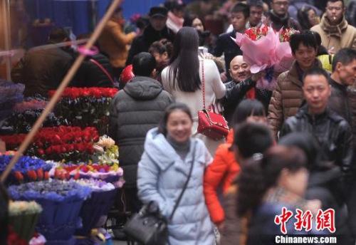 资料图:一男子举着鲜花穿梭在人群中。 陈超 摄