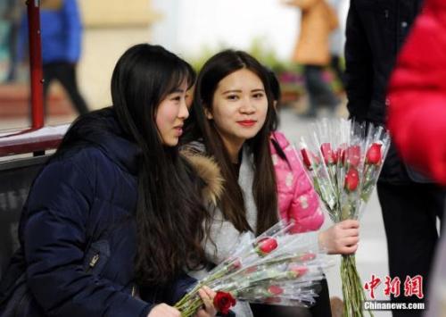 资料图:情人节当天,随处可见兜售玫瑰花的卖花女。 安源 摄