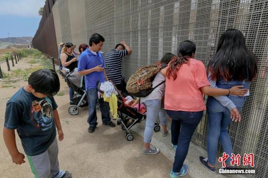 资料图 美墨边境两边的亲人隔着栅栏相聚。