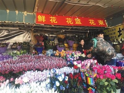 昨日,三元桥一处花店,一位男士在挑选鲜花。