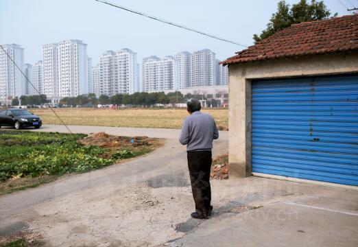 村里的不少村民在等着拆迁,远处的高楼一步步逼近曾经的田地和村庄。
