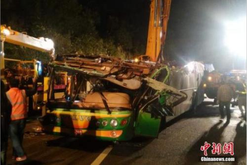 2月13日晚,台湾台北市靠近南港区一带发生游览车翻覆事故。经紧急救援,车上有32人明显死亡,10余位伤者送医抢救。图为消防队将事故车辆吊起、扶正。 中新社记者 陈小愿 摄
