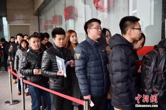 2月14日,北京市朝阳区民政局婚姻登记处前,一对新婚夫妻自拍晒出他们刚领到的结婚证。中新网记者 金硕 摄