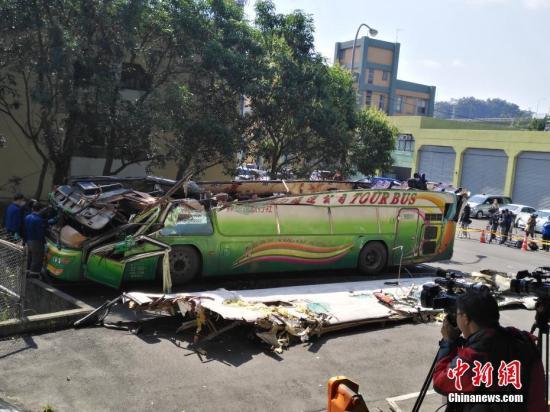 2月14日,在台湾高速公路局北区工程处木栅工务段院内的空地上,有关工作人员正在对游览车的车体进行现场勘验。中新社记者 陈林 摄