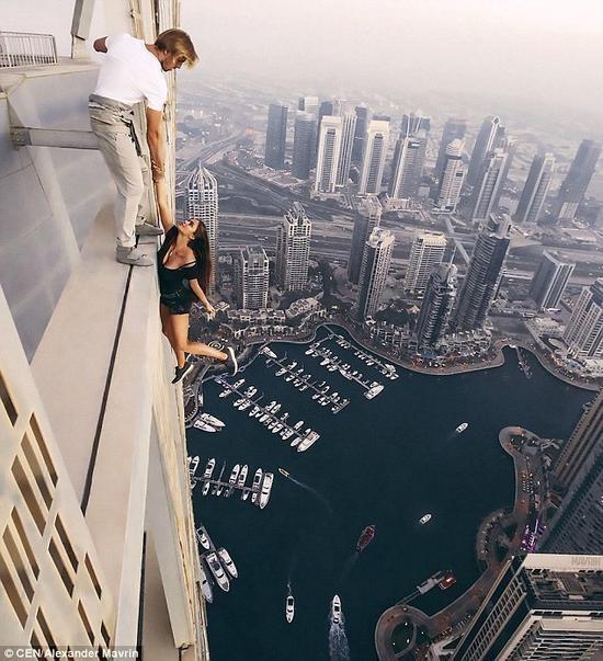 """用生命拍照!女模拽男子手在310米高楼""""荡秋千"""""""