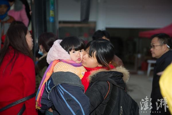 一位准备外出打工的母亲紧紧抱着自己的孩子。