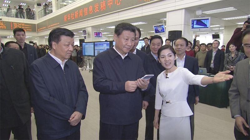 在新华社新闻信息发稿中心,习近平通过手机移动平台为新闻工作者点赞。