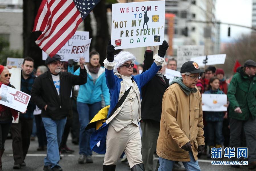 """2月20日,在美国纽约,人们参加抗议集会。每年2月的第三个周一是美国联邦法定假日――总统日,为纪念美国第一任总统华盛顿设立。今年的总统日,即2月20日,在华盛顿、纽约、洛杉矶、芝加哥等美国主要城市,大量民众走上街头,举行""""不是我的总统日""""集会,抗议特朗普政府在移民、环境等问题上的政策与举措。新华社/美联"""