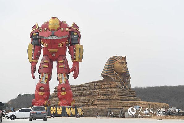 """2017年2月21日,在安徽省滁州市南谯区境内,""""山寨狮身人面像""""与高大的""""变形金刚""""吸引众多市民和游客慕名前来围观拍照。近日,一尊高近三十米的""""巨型变形金刚""""树立在世界知名建筑――""""山寨版狮身人面像""""旁边,恰似一名卫士在静静的守护。据悉,该狮身人面像是以埃及的狮身人面像为原型,身长约60米,身高约20米,按照1:1比例打造而成,是滁州长城国际影视动漫创意园标志性建筑。"""