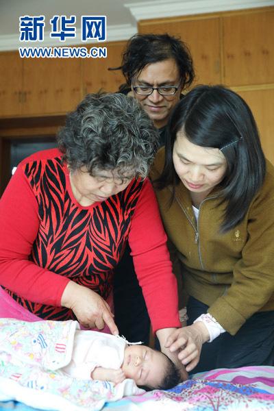 """这是雷森明(后)与家人一起哄女儿睡觉。(2017年2月5日摄)在中国呆了十二年,别人叫他""""中国通"""",他叫自己""""宋庄人""""--来自大洋彼岸的美籍印度人雷森明(Sridhar Ramasami),在北京宋庄这个中国原创艺术家聚居群落里当起了""""北漂"""",即便快到知天命的年纪,也依然活得兴高采烈:创作、策展、交各国朋友、娶中国媳妇,一个都没落。"""