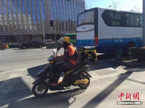 资料图:匆忙穿梭在路上的外卖小哥。中新网记者 刘湃 摄