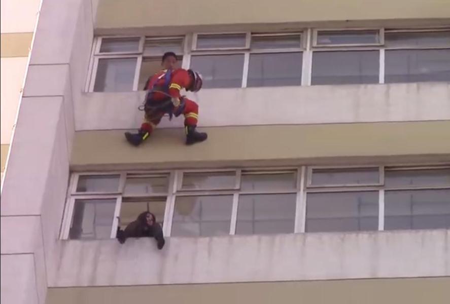 经过对现场形势的研判,消防员决定采用10楼悬垂速降,迅速将被困人员推进窗台内的救援方案。