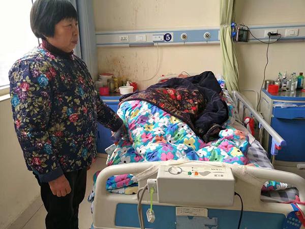 蒋女士和她躺在病床上的儿子孙桂军。