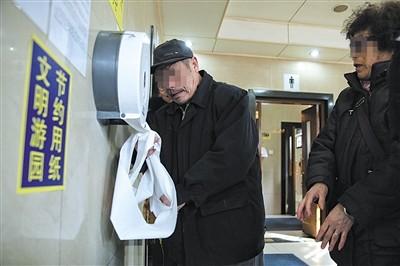 3月3日,英语手抄报 新年图一位市民正在天坛公园抽取免费厕纸。新京报记者 彭子洋 摄