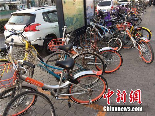 """两辆单车""""加塞""""停放,占用了部分公共道路。中新网 吴涛 摄"""