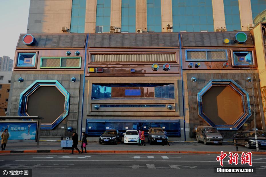 """2017年3月3日,沈阳市民从一街边巨型""""录音机""""旁走过。这台""""录音机""""位于沈阳的一环路上,目测估计足有四五层楼的高度,大概在十四五米左右。 视觉中国"""