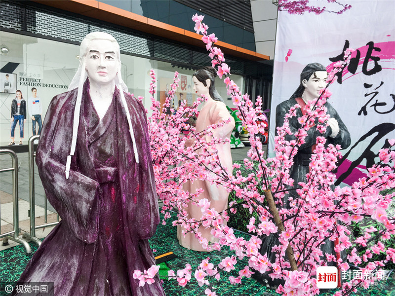 """这些蜡像位于绍兴上虞一家商场外广场的一场""""美食节"""",现场布置有桃花主题背景,写着三生三世十里桃花。"""