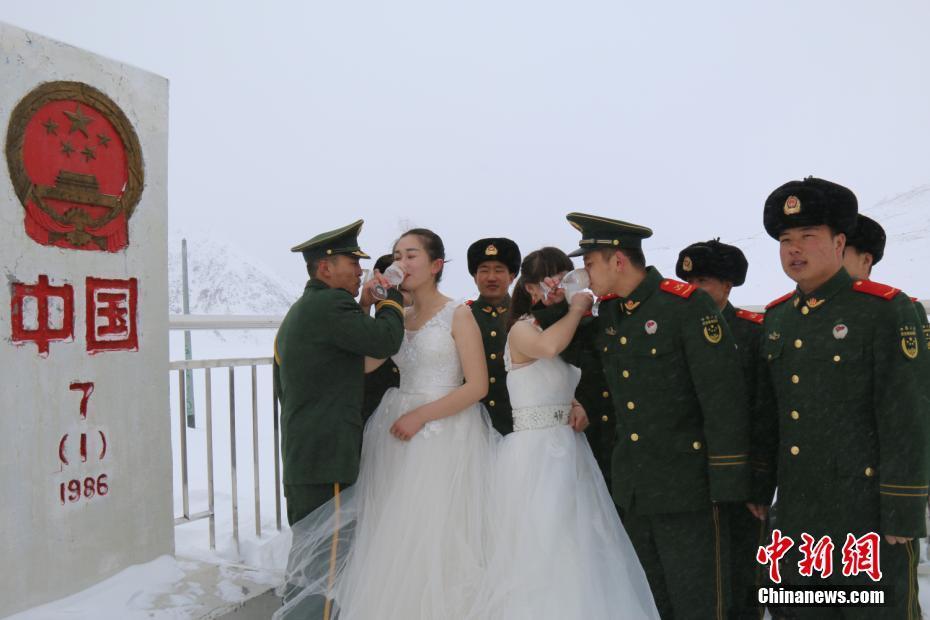 3月6日,武警新疆边防总队红其拉甫边防检查站为三名官兵在海拔5100米的中巴边界举行了简单而有意义的婚礼。图为新婚夫妇在喝交杯酒。 李康强 摄