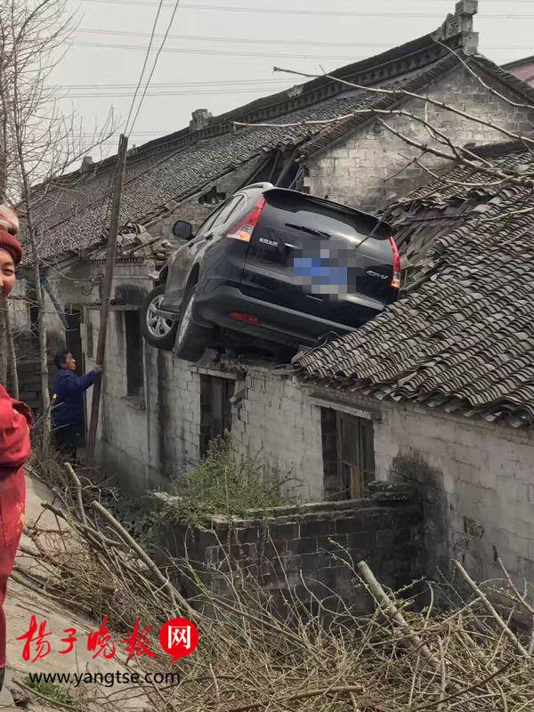 原标题:泰州离奇车祸:为避让三轮车 轿车飞上三米高屋顶