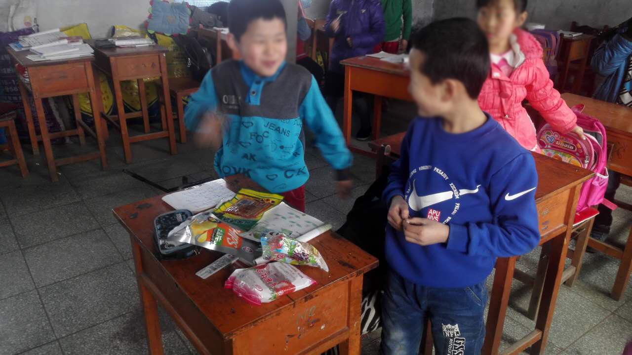 """某小学的学生正在课件分享山寨小零食。一位""""免费午餐""""公益团队志愿者说:""""那天看我女儿同学在吃五毛一包的辣条,一股特别诱人的奇香,因为全是过量的香精色素添加剂 。"""""""