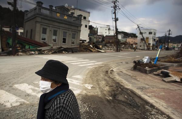 """2011年3月31日,日本气気仙沼市,行人站在街头。""""311""""特大地震引发的海啸几乎席卷了整个日本东北部地区,随后引发的福岛核电站爆炸更是让这一地区笼罩在核灾难的阴影下。日本警察厅31日宣布,截至当天10时,日本东北部海域发生的强震及其引发的海啸已确认造成11417人死亡,16273人失踪。这也是日本自二战以来损失最为惨重的一次。 视觉中国 资料图"""
