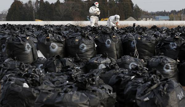 当地时间2015年2月24日,身穿防护衣和戴面罩的工作人员在福岛核电站附近富冈町处理装有被污染的泥土和树叶的大袋子。 视觉中国 资料图